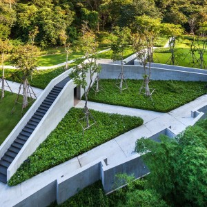 Inspired by the nearby mountain range, Khao Yai, Thailand's largest rain forest, the landscape is created as the link between the architecture and Nature. Instead of trying to produce a faked natural forest, the architecture is interpreted as big trees while the landscape represents the green areas underneath.
